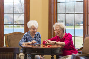 Two senior women in assisted living playing checkers