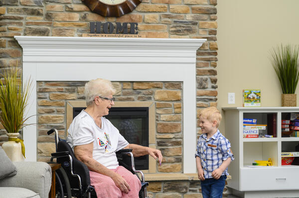 Senior woman spends time with grandson in assisted living