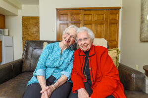 Two senior women smile and spend time together in assisted living