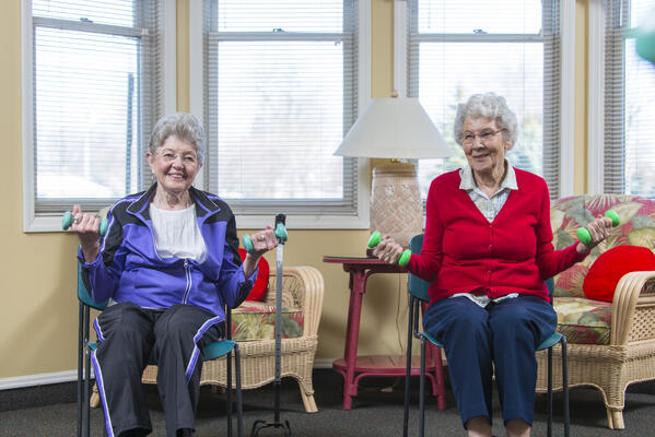 Two senior women work out with small weights