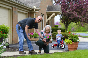 Retired couple planting flowers with grandson