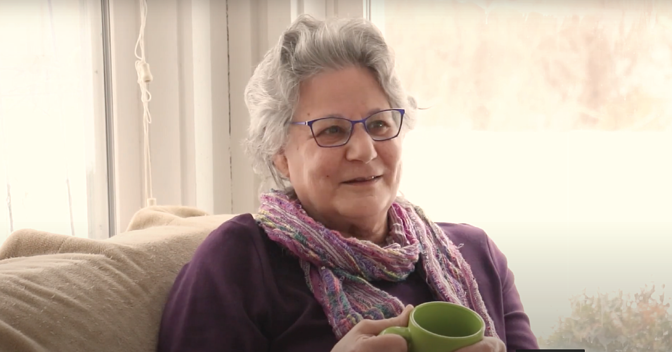 Otterbein Lebanon resident Linda F. sitting on the sofa in her living room smiling and holding a green coffee mug.