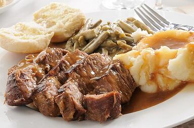 Pot roast, green beans, mashed potatoes and biscuit on plate