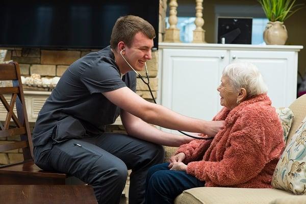Male nurse listens to elder's heartbeat with stethoscope