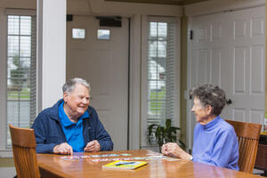 Senior man and woman play game together in assisted living