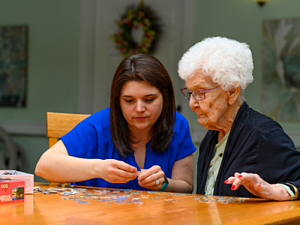 Nurse and female senior put together a puzzle during a respite care stay at otterbein