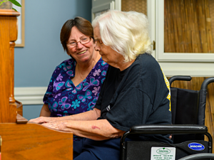 Senior and caregiver play piano during respite care stay at otterbein seniorlife