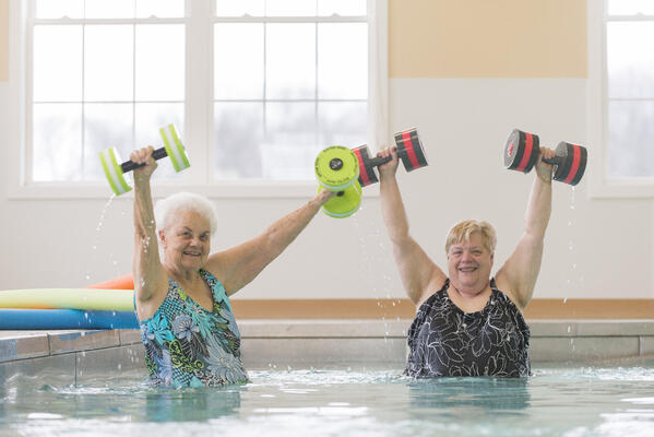 Two senior women work out in indoor pool