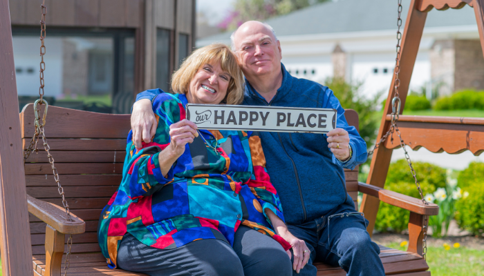 """Couple at Otterbein SeniorLife in Franklin, Indiana, hold sign saying """"our happy place"""" after downsizing their house"""