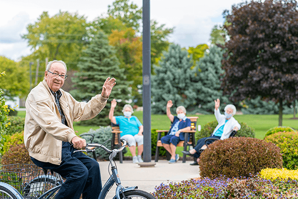 Otterbein Marblehead resident on a bike ride waving to the camera with other residents in the background also waving to the camera.