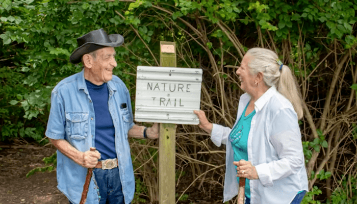 Otterbein Lebanon residents Stew and Judy S. next to the nature trail sign.