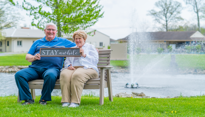 """Otterbein St. Marys couple sits on the bench near the shores of Grand Lake St. Marys holding sign saying """"Stay awhile."""""""