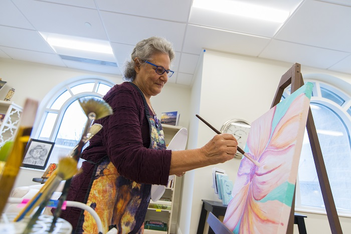 Creative senior woman at Otterbein paints on easel