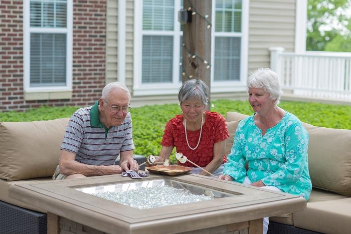Three seniors roast marshmallows over fire pit outdoors at Otterbein